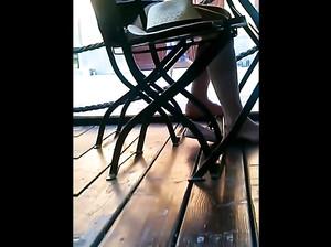 Скрытая камера снимает стройные ножки девушки за столиком в кафе