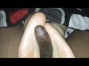 Белая шмара дрочит ступнями ног черный член