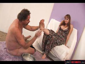Послушный голый раб моет ноги госпоже, а та смачно курит