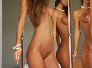 Худенькая порно звезда Nessa Devil стоит голой перед зеркалом и рассматривает свое тело