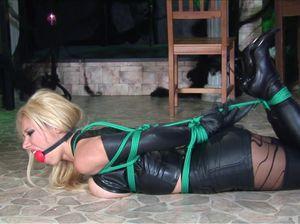 Блондинка с кляпом во рту лежит на полу в кожаном черном нижнем белье