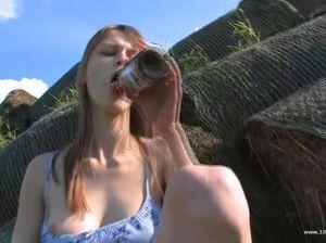 Привлекательная девушка мастурбирует попу бутылкой на природе