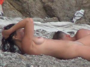 Развратник на нудистском пляже посматривает за грудастой брюнеткой