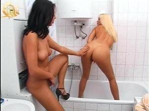 Две лесбиянки играют в ванной со страпоном