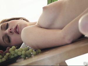 Юная девушка теребит киску на столе среди фруктов