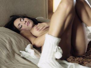 Темноволосая нежится на кровати и показывает свою лысую пизду