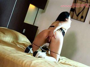 Черноволосая красотка ласкает киску в своей спальне
