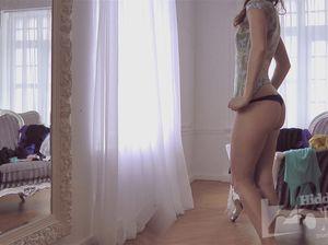 Худышка перед зеркалом одевает белье и майку