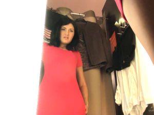 Симпатичная брюнетка переодевается в красное платье