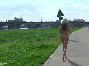 Очень худенькая девушка позирует голой на улице