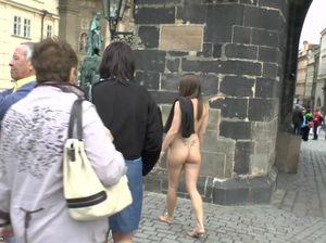 Туристка без одежды прогуливается по достопримечательностям старинного чешского города