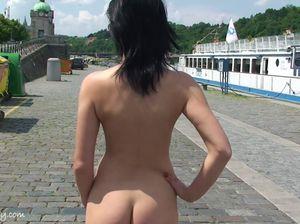 Красивая брюнетка на спор прогуливается по набережной без одежды