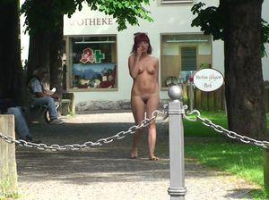 Красивая голая девушка бродит людными улицами города
