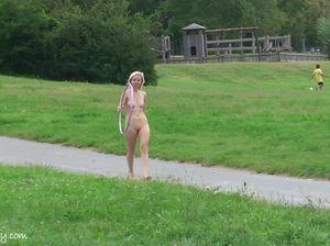 Худенькая блондинка позирует голой перед камерой в парке