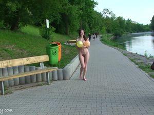 Нагая девушка ходит по парку с воздушными шариками