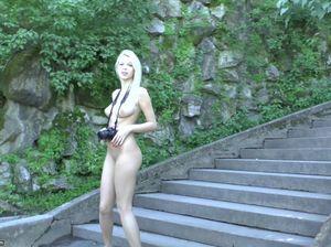 Красивая блондинка голая прогуливается по парку с фотоаппаратом на шее
