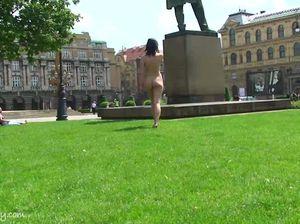 Изящная красотка с голыми сиськами и попой прогуливается по городскому парку