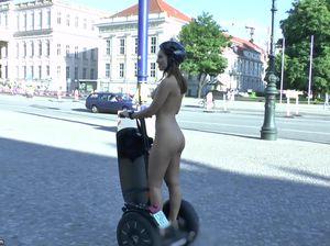 Обнаженная телка в шлеме катается на сигвее по городу
