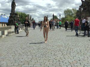 Туристка без одежды осматривает достопримечательности