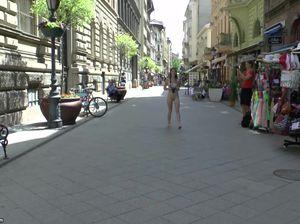 Красивая голая девушка привлекает к себе внимание в центре города