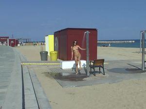 Обнаженная красотка ходит по пляжу