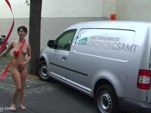 Брюнетка с короткой стрижкой и татуировкой на пилотке голой гуляет по улице, играя с фигурной ленточкой
