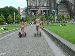 Две телки катаются на сигвеях по парку и площади