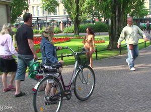 Симпатичная девка гуляет голой в людном месте и светит шикарной попкой