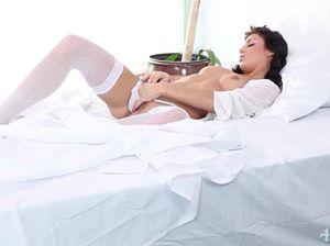 Девушка в сетчатых белых чулках легла на кровать и ласкает киску пальцами и дилдо