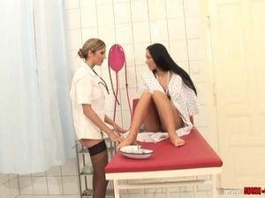Медсестра в чулках проводит осмотр бритой киски своей пациентки