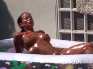 В надувном бассейне грудастая загорелая девушка прыгает на члене любовника попой