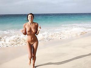 Знойная голая девушка на пляже демонстрирует свои красивые формы