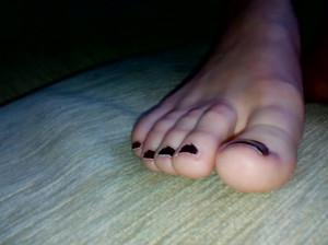 Малышка красит свои ногти на ногах и снимает на камеру