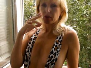Фигуристая блондинка в откровенном купальнике курит у окна