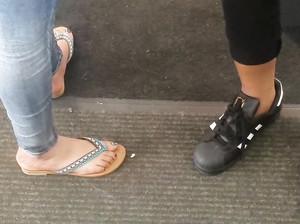 Чувак тайком снимает ноги девчонки в джинсах